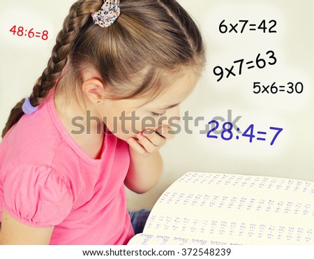 A girl about ten years yawns, looking into a large notebook with math problems. It gives examples of the multiplication tables. - stock photo