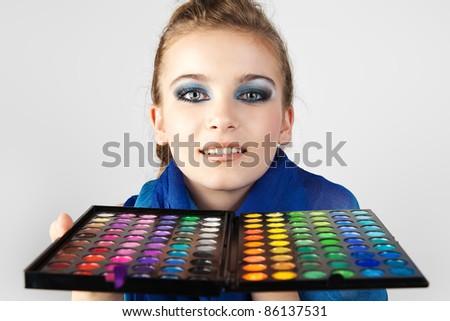 A girl admires make-up collection for creative visage. - stock photo