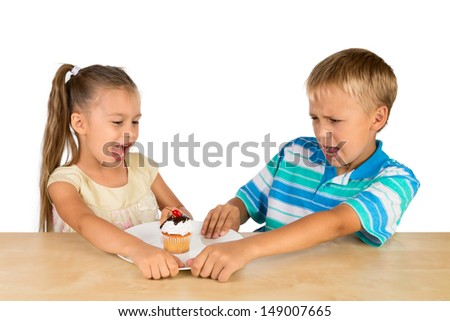 A  girl and a boy are fighting over a single delicious cupcake