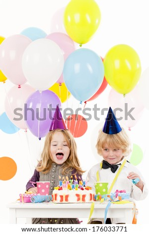 A girl and a boy blowing out their birthday candles with several balloons floating above.