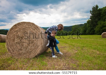 A girl and a boy pushing a round bundle of straw. - stock photo