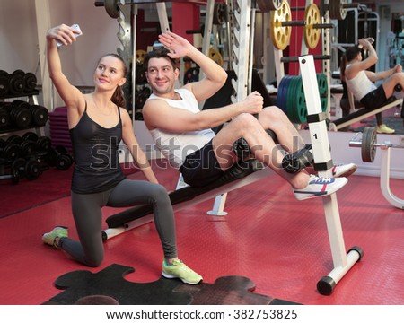 A girl and a guy are in the gym and take pictures - stock photo