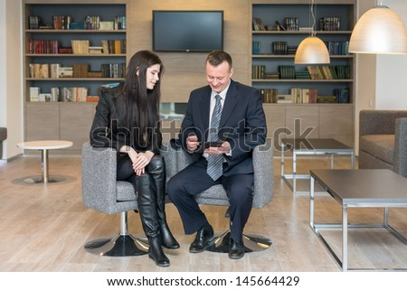 A girl and a man in business suits sitting on chairs with notepad