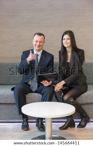 A girl and a smiling man in business suit sitting on a sofa with a laptop and making thumbs up