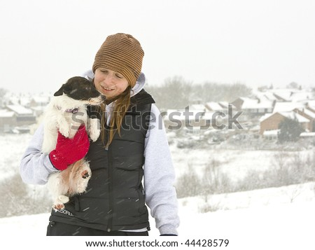 A girl and her dog enjoying the snow