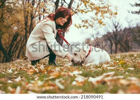 A girl and her dog (Labrador retriever) walking in a park in autumn  - stock photo