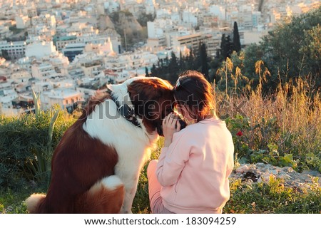 A girl and her dog sitting on a mountain at sunset and looking at each other's eyes.Real warm light from sunset. - stock photo