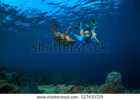 A girl and turtle underwater