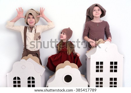 a girl and two boys playing with toy houses - stock photo