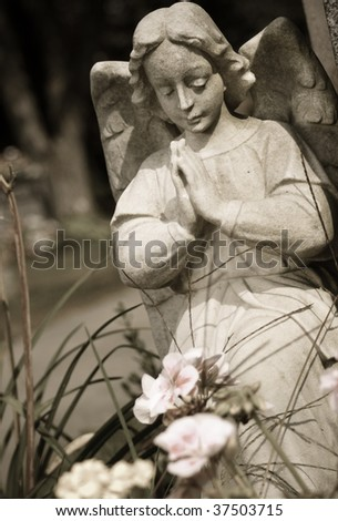 A girl angel kneeling and praying - stock photo
