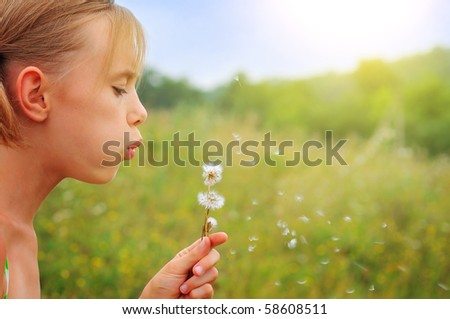 A girl blowing a dandelion flower against a background of green spring grass.