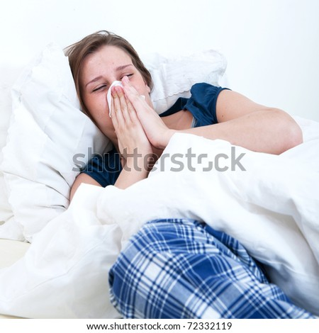A girl blowing her nose while lying sick in bed. - stock photo