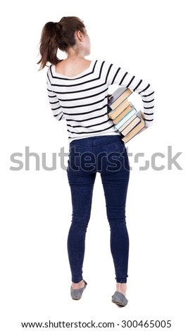 A girl carries a heavy pile of books. back view. Rear view people collection.  backside view of person.  Isolated over white background. Frenchwoman in vest is holding a stack of books under his arm. - stock photo