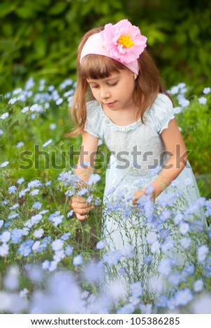 a girl child about flax flowers - stock photo