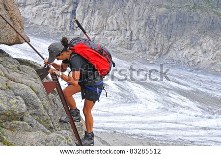 a girl climber ascends a steep ladder over a long drop. In the background a glacier - stock photo