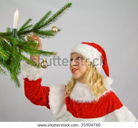 A girl, decorating the Christmas tree - stock photo