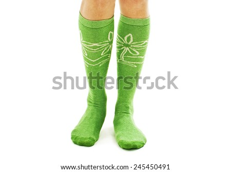 A girl dressing green-white socks. Isolated on white background  - stock photo