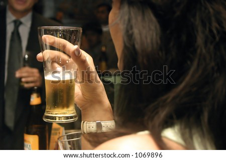 A girl drinking beer at a party - stock photo