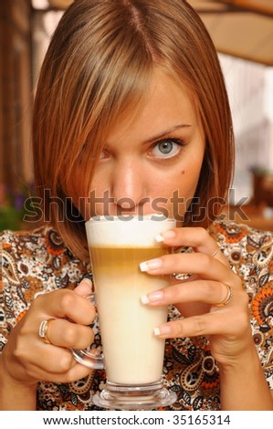 a girl drinks cappuchino in a cafe