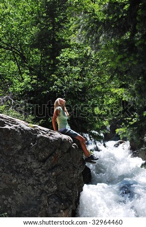 A girl enjoying the sun next to a waterfall. - stock photo