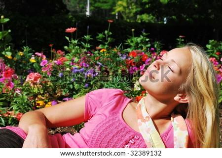 A girl enjoys a summer day in a flower garden. - stock photo