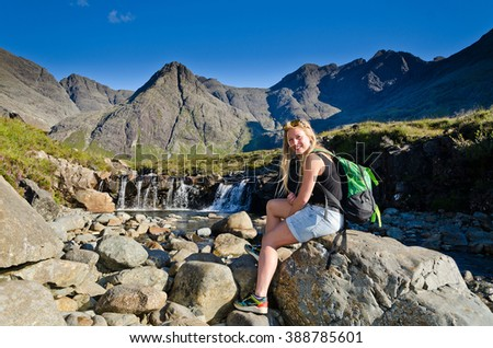 A girl enjoys the view on the beautiful Fairy Pools on the Isle of Skye, Scotland