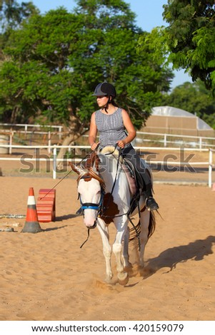 A  girl getting a horseback riding lesson