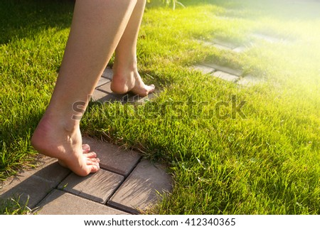 A girl goes on a path in a garden - stock photo