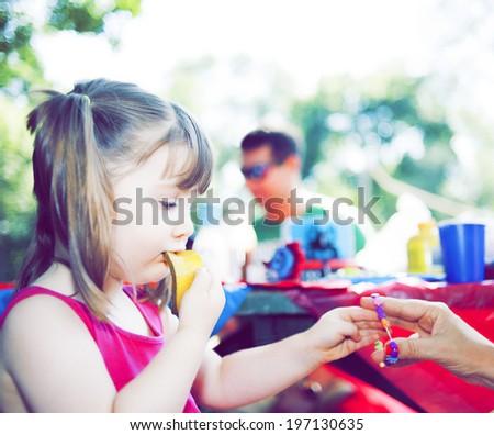 A girl having a bracelet put on her wrist. - stock photo