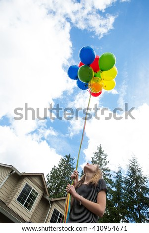 A girl holding a cluster of colorful balloons - stock photo