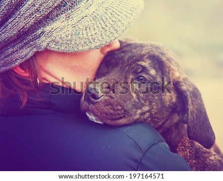a girl holding a pit bull mix puppy done with a retro vintage instagram filter  - stock photo