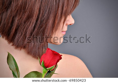 A girl holding a red rose in her hand. - stock photo
