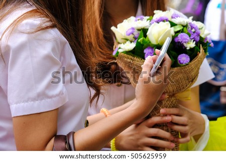 A girl holding mobile phone withbackground of another girl holding bouquet of colorful flowers.