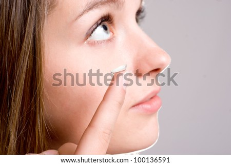 A girl holds a contact lens, focus on the lens - stock photo