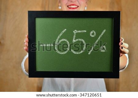 a girl holds a sign saying sale - 65 percent - stock photo