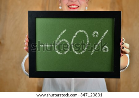a girl holds a sign saying sale - 60 percent - stock photo