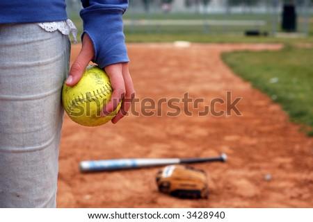 A girl holds a softball on the infield diamond. - stock photo