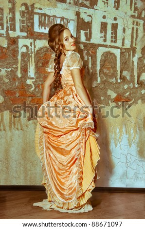 A girl in a ball gown stands near the wall