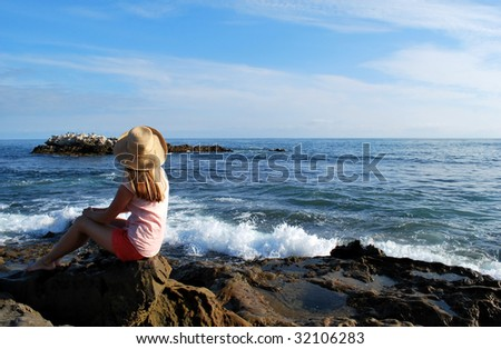 A girl in a big hat sits looking over the beach at Laguna Beach, CA. - stock photo
