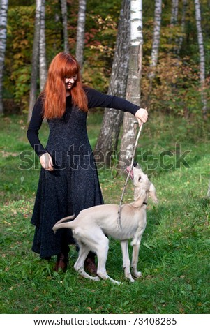 A girl in a black dress and white saliki pup in a forest