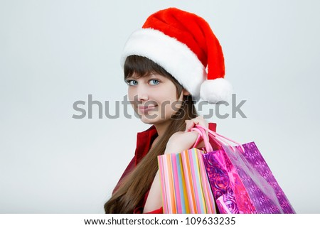 A girl in a Christmas hat with shopping