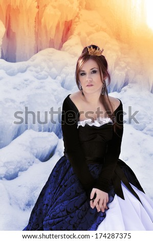 A girl in a dress and a icicle on a winter landscape - stock photo