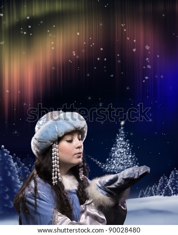 A girl in a fairy dress conjures in Christmas forest. Her breath makes glowing a little Christmas tree.