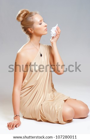 A girl in a gold dress holding a flower in her hand.