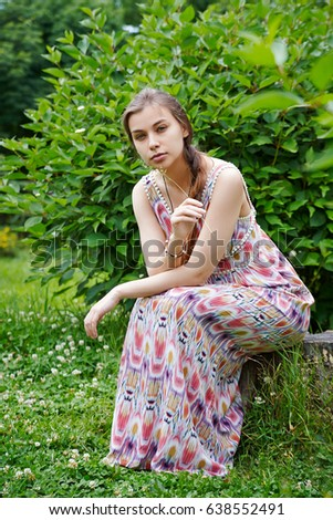 A girl in a long dress is sitting on a stump