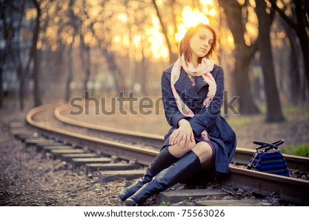 A girl in a park near the railway at sunset - stock photo