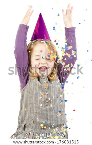 A girl in a party hat throwing confetti.