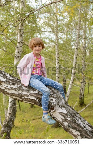 A girl in a pink jacket sitting on an old tree