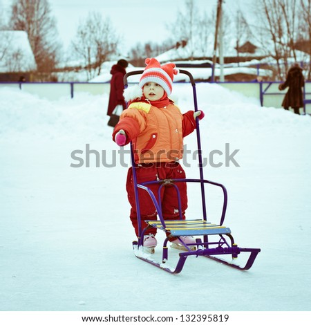 A girl in a red jacket skates on the ice. - stock photo