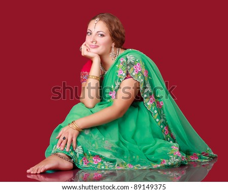 a girl in a sari sitting on the floor
